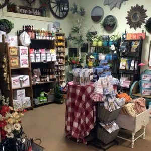 Country store display of gourmet foods, kitchen towels and wall art