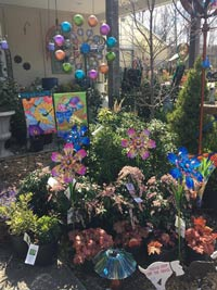 shrubs with colorful garden art