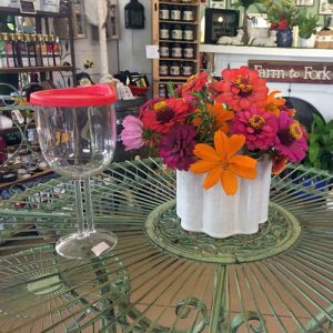 bistro table with colorful flowers and shatterproof wine glass