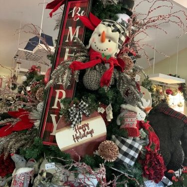 holiday Christmas shop open with decorated trees, ornaments, decor and gifts