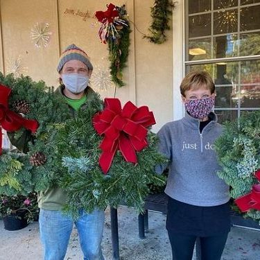 Garden Hut staff holding beautiful Christmas wreaths with bows
